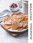 Small photo of Freshly baked homemade heart shaped Belgium waffles on gray background. European baked pastry sweets. St. Valentine's Day breakfast concept.