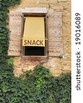 A snack bar sign in France above a window in a wall with ivory - stock photo