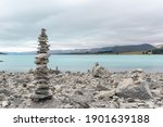 Tall, narrow, rock cairn on the shore of Lake Tekapo, Mackenzie District, New Zealand. The lake and mountains in the background.