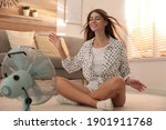 Small photo of Woman enjoying air flow from fan on floor in living room. Summer heat
