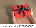 a woman holding a red gift box... | Shutterstock . vector #1902008005