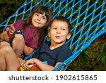 Children Sit In A Hammock. Boy...