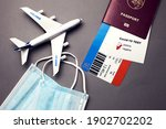 Small photo of Traveling during COVID-19 pandemic, passport with airline ticket, covid-19 negative test, medical masks and plane on grey background, airport security health and safety check concept