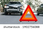 Small photo of Red emergency stop triangle sign on road in car accident scene. Broken SUV car on road at traffic accident. Car crash traffic accident on city road after collision. Long web banner