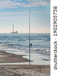 Small photo of Fishing rod, upright on sandy beach along a barrier island, in view of offshore dredger with tower (maybe for mining sand for beach nourishment) in the Gulf of Mexico. An example of juxtaposition.