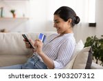 Small photo of Young indian woman shopper sit on couch enjoy easy paying for goods online using bank card phone. Happy mixed race female traveler book tickets trip hotel at travel agency transport operator website