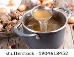 Small photo of Saucepan with bouillon with a ladle on the table. Bone broth