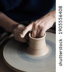 Small photo of Woman starts to create a ceramic cup on the pottery wheel. Working with clay on potter's wheel, closeup of hands, crafts and arts. Anonymous hands at work. Hobby and leisure with pleasure concept.