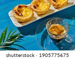 Small photo of Pasteis de nada and an glassy espresso cup on deep blue wooden boards. a fern twig is on the right edge