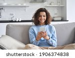 Small photo of Happy hispanic teen girl looking at smartphone relaxing on couch at home, enjoying using online mobile apps technology, playing games on cell phone, checking messages or social media posts.