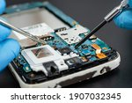 Small photo of Technician repairing inside of mobile phone by soldering iron. Integrated Circuit. the concept of data, hardware, technology.