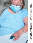 Small photo of adulto mayor mujer abuela vestida de azul monitorea su nivel de oxigenacion en casa para mantenerse saludable en esta pandemia