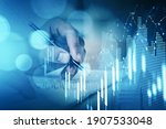Small photo of Businessman hand drawing virtual chart or collect stock market rates into notebook to make a forecast. Double exposure. The concept of successful investment decision