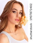 Small photo of A beautiful young girl holds a yellow flower - a rose - near her face and looks into the camera. Close-up portrait of a beautiful girl with a flower near her face. Girl model on a gray background, clo