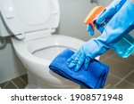Small photo of close up hands women wearing protect glove blue using liquid cleaning solution cleaning flush toilet, disinfection and hygiene concept