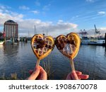 Couple holds two heart shaped Waffles on a wooden sticks with powdered sugar and chocolate on blurry background of river Elbe and Hamburg port