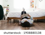 Small photo of Studious adolescent girl reading a book and enjoying a story in her bedroom. Young teenage girl lying on the floor with her feet up on her bed