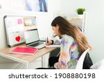 Small photo of Studious adolescent girl writing on a notebook and doing her homework. Smart teenage girl sitting on her bedroom desk and doing school work