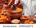 Small photo of Grandmother's hand in jewelry, using a wooden soup ladle, pours horse milk, koumiss in a wooden bowl. Traditional Kazakh ware for Kumis. Nauryz. Dastarkhan. Festive table.