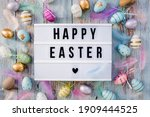 Small photo of Stylish text frame of the lightbox with the inscription happy easter. Pink, blue, white, gold, and yellow eggs are everywhere. Colorful Easter eggs top view. Copyspace.