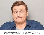 Studio close-up portrait of funny confused blond mature man making crazy goofy face, with crossed eyes, expressing puzzlement, feeling bewilderment. Headshot over gray background