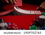Small photo of Casino. Poker. The player's hands shuffle the deck of playing cards. Game chips and dice lie on the table against a red background. Game chips for betting in gambling. Dice. Poker chips.