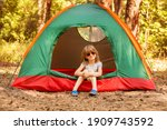 Little girl in sunglasses smile and looking at camera playing in tent on campsite, happy girl sitting inside tent in forest