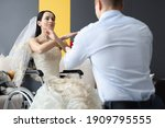 Small photo of Woman in wedding dress makes negative gesture to groom. Who are the gigolo and how to recognize him concept