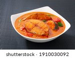 Small photo of Fish curry_Seer fish curry ,traditional Indian fish curry ,kerala special dish using coconut ,arranged in a white bowl garnished with curry leaves on black textured background, isolated.