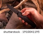 Small photo of Knife in hand. Folding knife in hand. Pocket knife in hand. Black pocket knife.