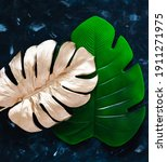 Small photo of golden and green artificial monstera leaves on blue background, concept of home decor and luxury vs simpler products