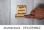 Small photo of Equity, diversity, inclusion and belonging symbol. Wooden blocks with words 'equity, diversity, inclusion, belonging' on beautiful grey background. Diversity, equity, inclusion and belonging concept.