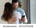 Small photo of Lack of trust in relations. Suspicious jealous boyfriend hug girlfriend checking her phone calls contacts behind back. Unfair husband cheating wife simulate love while reading messages from mistress