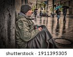 Homeless Man Sits On A Wall Of...