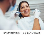 Small photo of Over the shoulder view of a dental doctor treating female patient. Female having routine dental checkup at dentist.