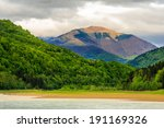 view on lake shore near the forest on mountain background - stock photo
