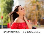 Side profile photo portrait of cheerful woman smiling laughing touching neck spending free time walking on city streets in windy weather