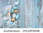 Small photo of Gold, black, white, blue Easter eggs in a string bag on a blue wooden background. Geometry. The minimal concept of Easter. Top view. An Easter card with a copy of the place for the text.