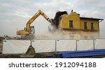 Yellow excavator destroys an old building. Heavy duty machine is demolishing a brick building.