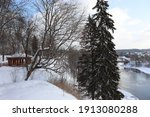 Beautiful winter landscape. Picturesque trees on the hillside. Tall spruce and deciduous tree with a spreading crown. A calm river, snowdrifts and a wooden gazebo. Wonderful nature in the park.