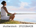 young woman meditating near...   Shutterstock . vector #1913186428