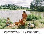 Woman And Boy Sitting Near Lake ...