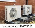 Small photo of Two air source heat pumps installed on the exterior of a modern house