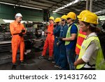 Small photo of Skillful worker attending brief meeting in the factory . Industrial people and manufacturing labor concept .