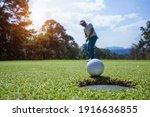 Blurred Golfer Putting Ball On...
