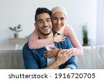 Portrait of cheerful muslim couple embracing at home, copy space, closeup. Smiling young woman in headscarf hugging her loving husband from behind, middle-eastern family spending time together