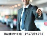 Smiling Car Salesman Handing...