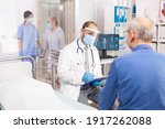 Small photo of Doctor wearing visor as safety precaution in the course of consultation of senior man. Physician practitioner in the course of private modern clinic appointment during coronavirus pandemic.