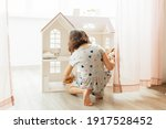 Girl Playing With Doll House In ...