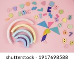 Small photo of Wooden baby toys on a pastel pink background. Rainbow, numbers, blocks, puzzle shapes Set of accessories for children. Early education, imagination, grasping training. Flat lay, top view